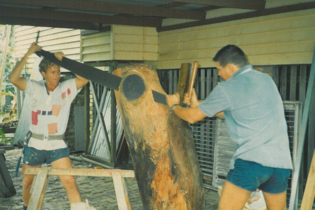 Kevin Hattin using a hand saw to cut a log