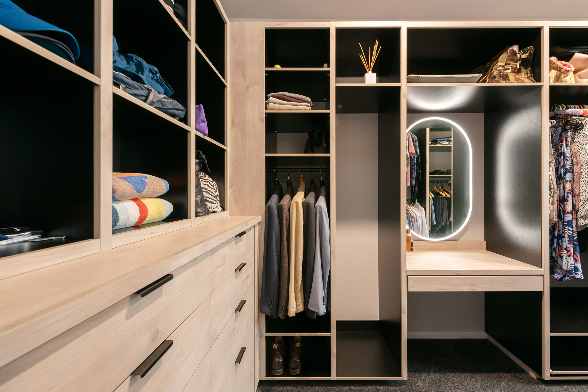 Custom woodgrain and black walk in wardrobe with oval mirror and integrated lighting