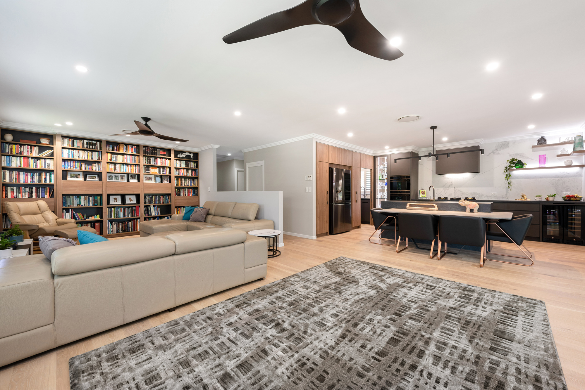 Open plan kitchen living and dining room built in bookcase and industrial styled kitchen