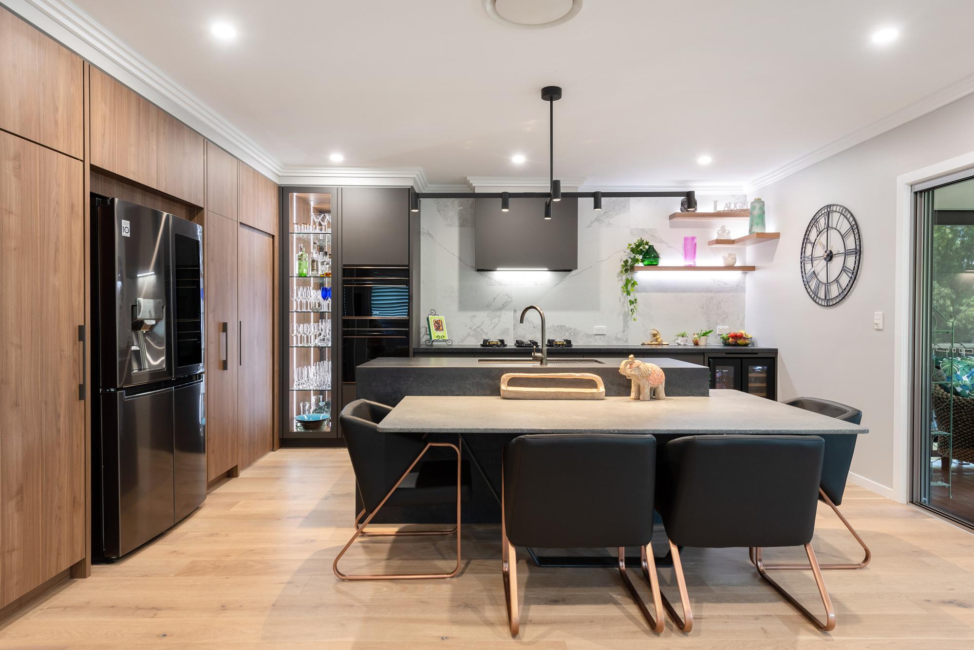 Modern industrial kitchen, concrete benchtops, marble tile splashback, feature timber cabinetry, black pendant light, glass display unit