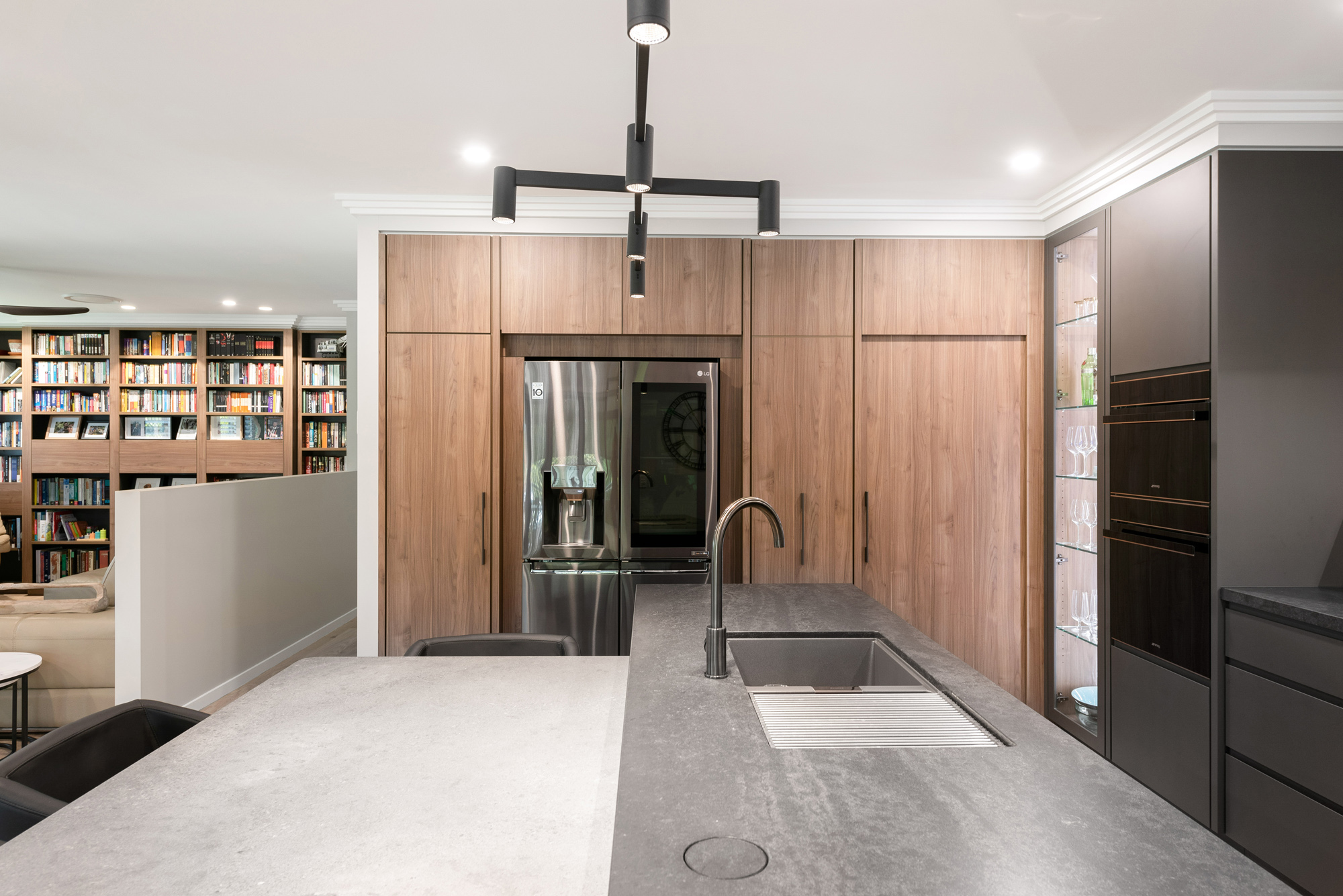 Modern industrial style kitchen island bench with concrete benchtops, woodgrain pantry wall, black french door fridge and black feature light
