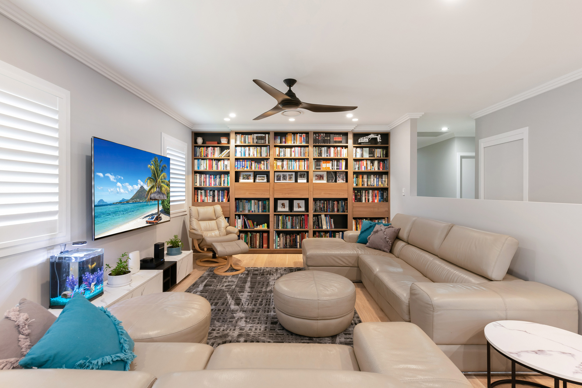 Living room with custom woodgrain built in bookcase, cream couch and wall mounted tv